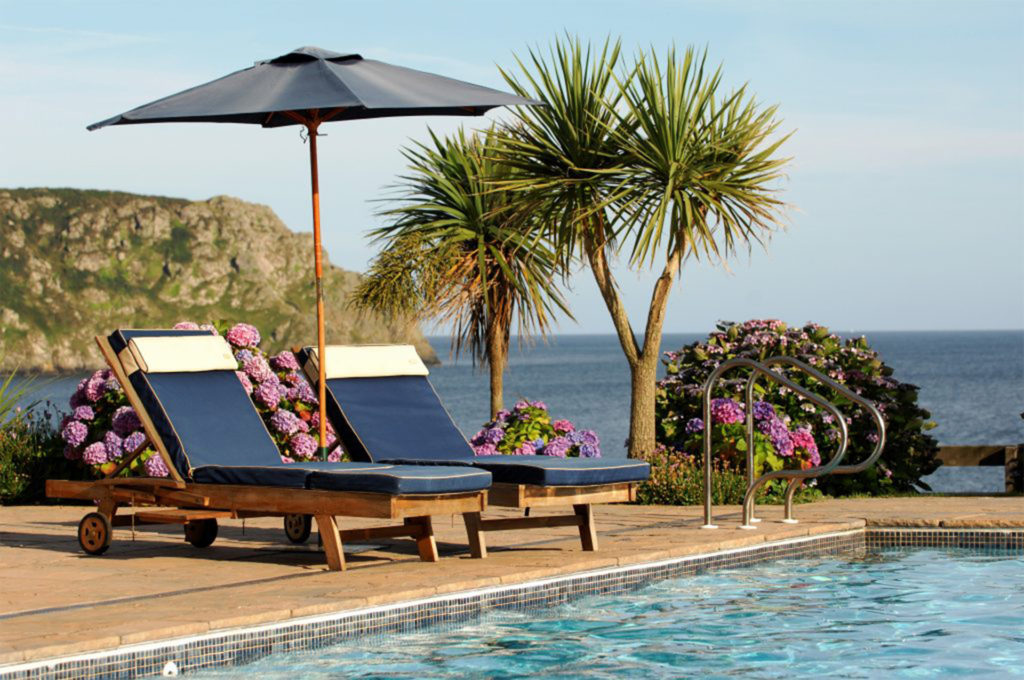 Sun loungers, palm trees, pool and sea beyond