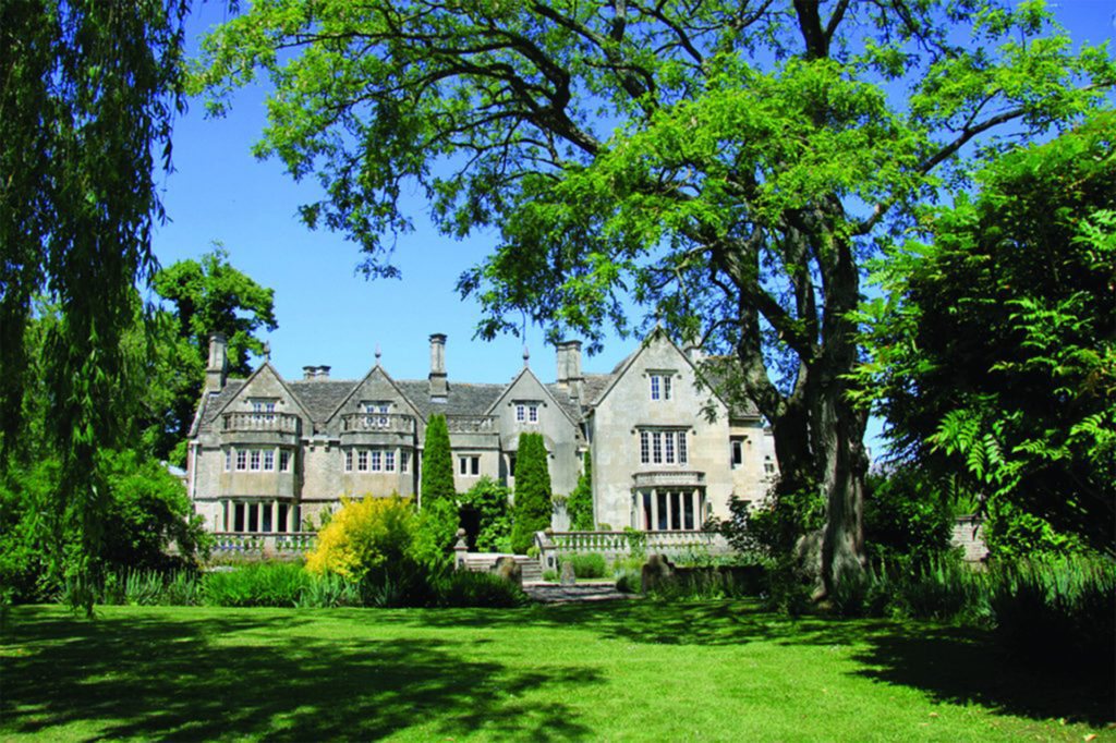 Tradiional grey stone building with mullion windows, seen through lush green trees and gardens