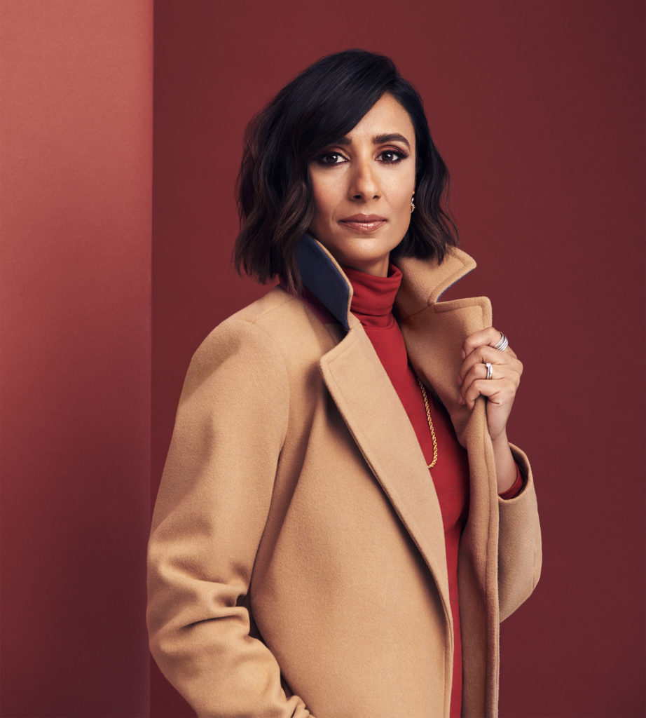 Young Asian woman in smart camel coat over red roll neck top, terracotta background