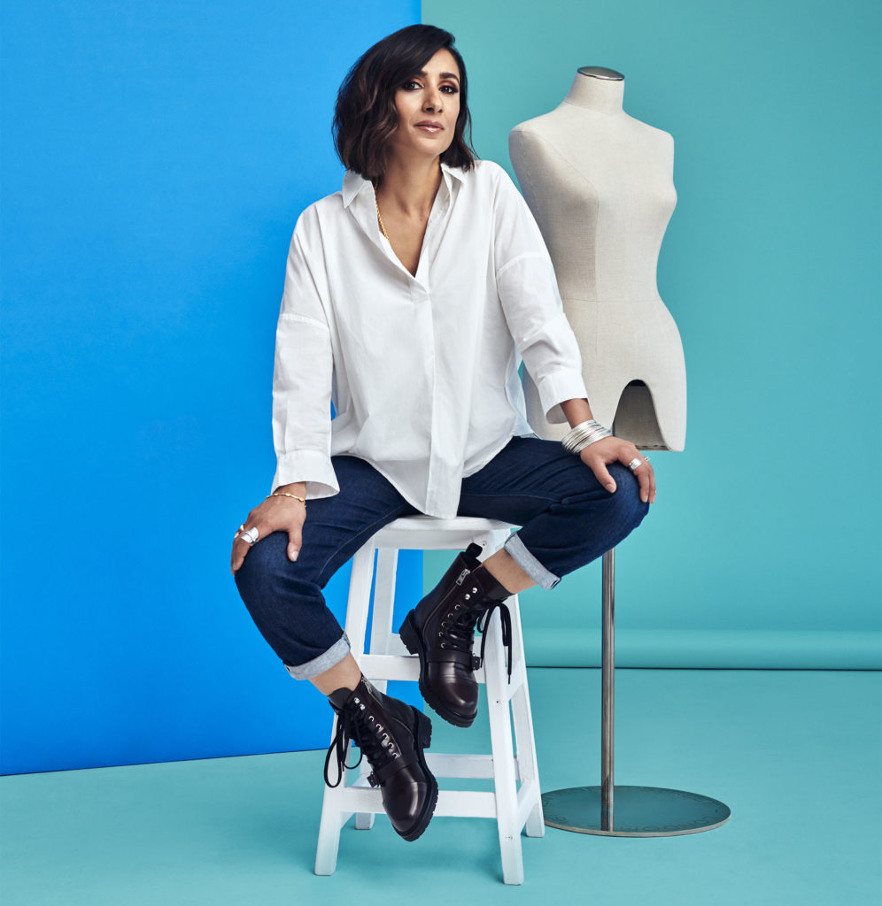 Young Asian woman in white shirt, dark skinny jeans and lace-up ankle boots, blue and turquoise background