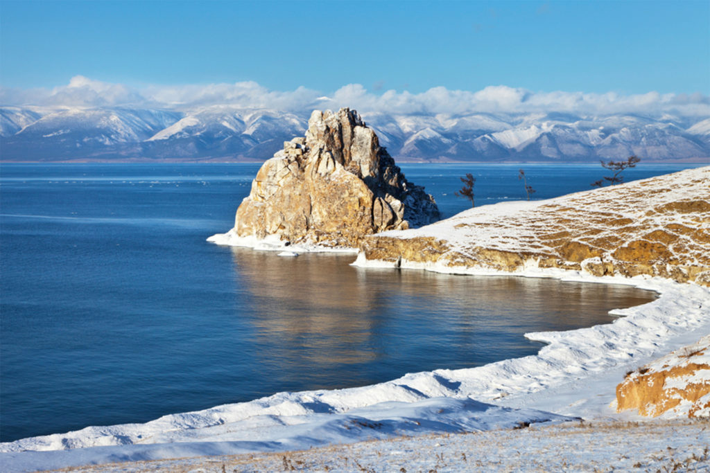 Snow on rocky landscape, castle on outcrop, blue lake and cloud-topped mountains beyond