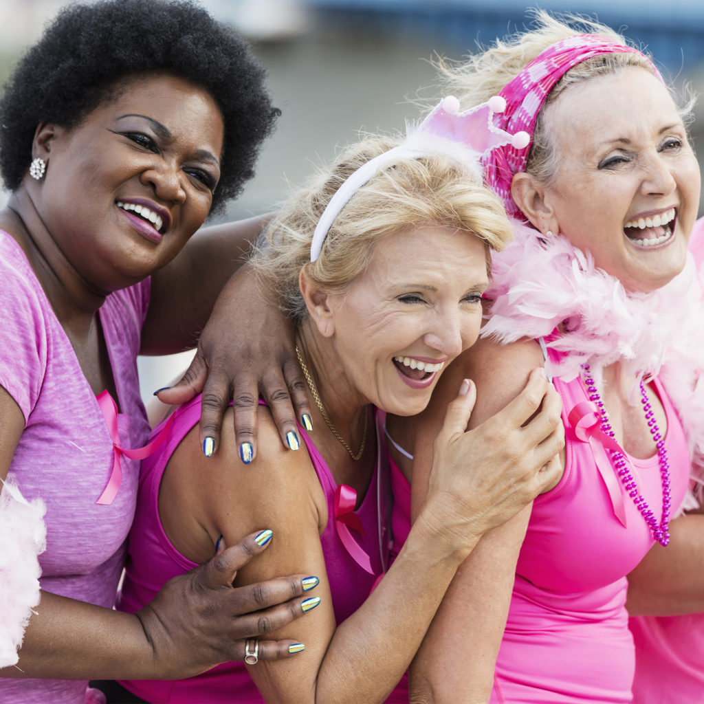 Women in pink sports gear and feather boas, raising money for breast cancer charities