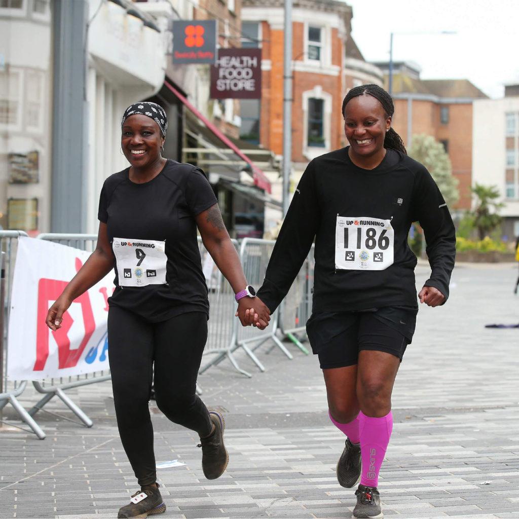 2 black women competing in fun run through town