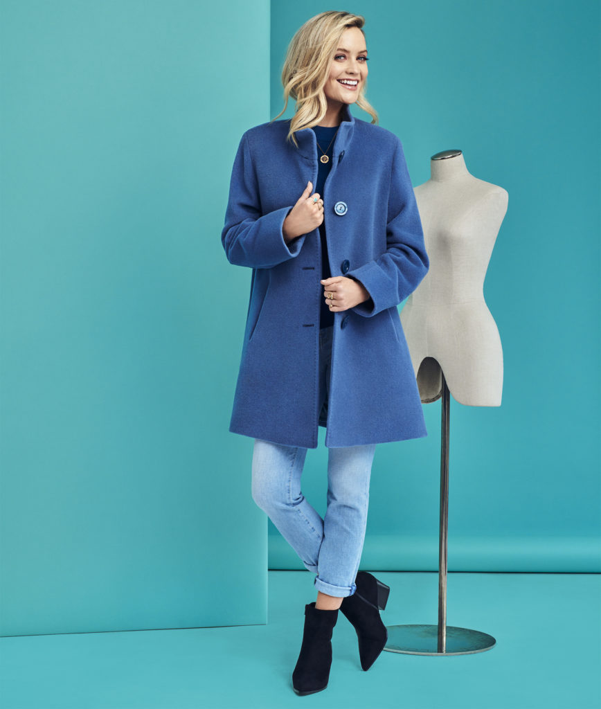 blonde woman in blue coat with lapels and blue jeans
