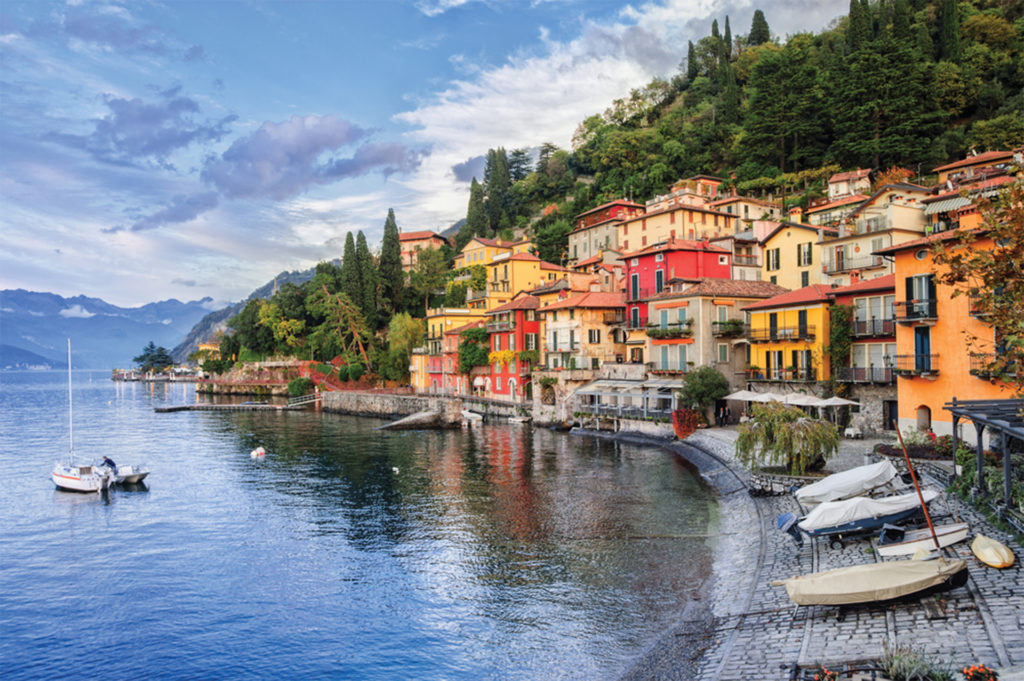 Red and yellow Italian style buildings at water's edge, wooded mountain behind, small boats on sloping cobbled foreshore