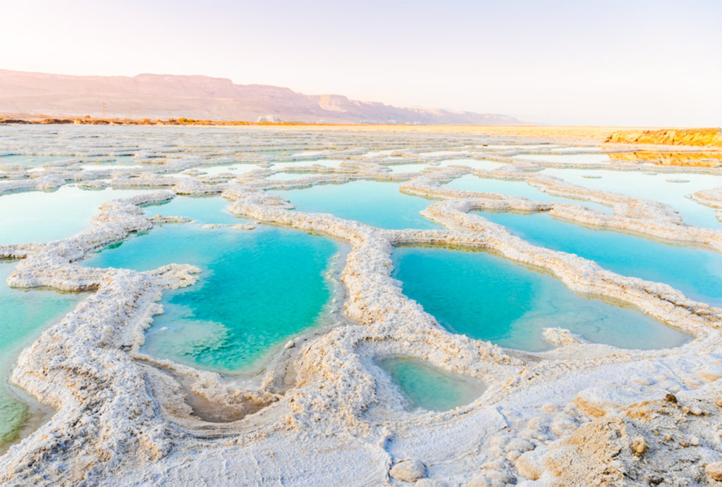 Series of turquoise pools with white salty edges, arid land beyond