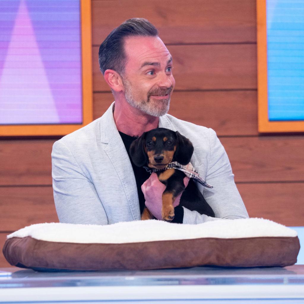 ?Actor Daniel Brocklebank from Coronation Street in Loose Women TV studio cuddling alert black and tan miniature dachshund.