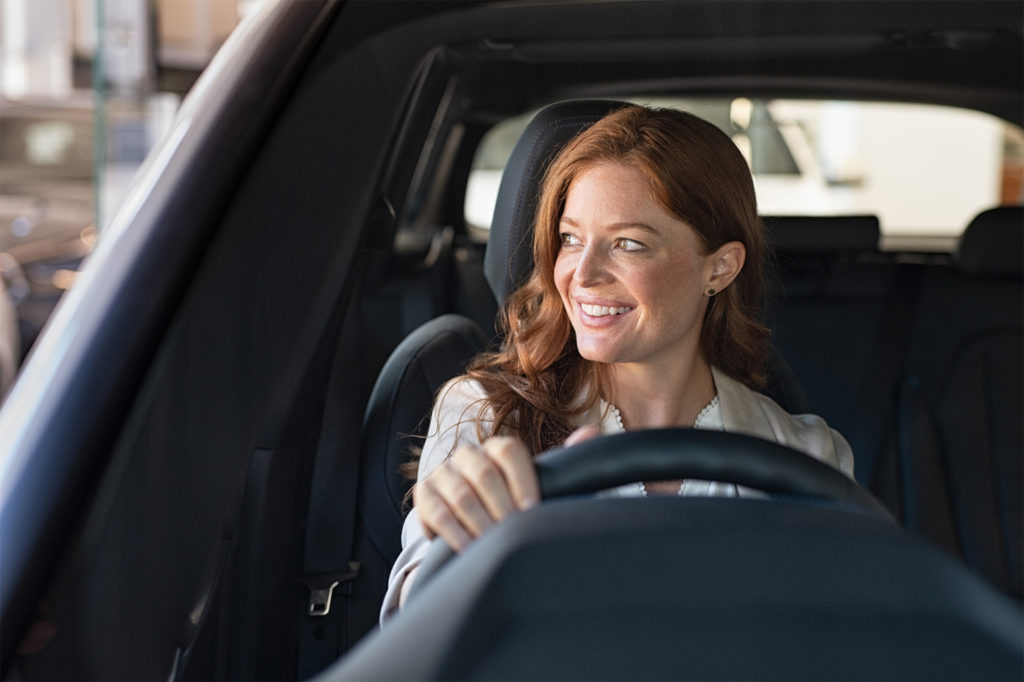 Happy woman in 30s driving
