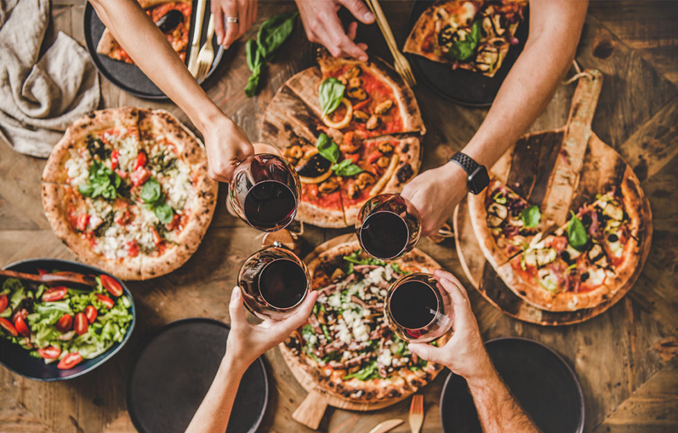 Pizzas on table, 4 people reaching across to clink glasses of red wine, seen from above