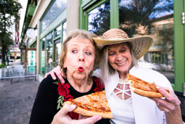 2 mature women eating street food pizza, pulling funny faces, guilty pleasure