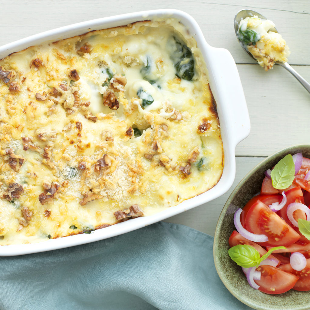 Oven dish of cheese topped bake, one spoonful out showing spinach and cauliflower, dish of tomato salad on side