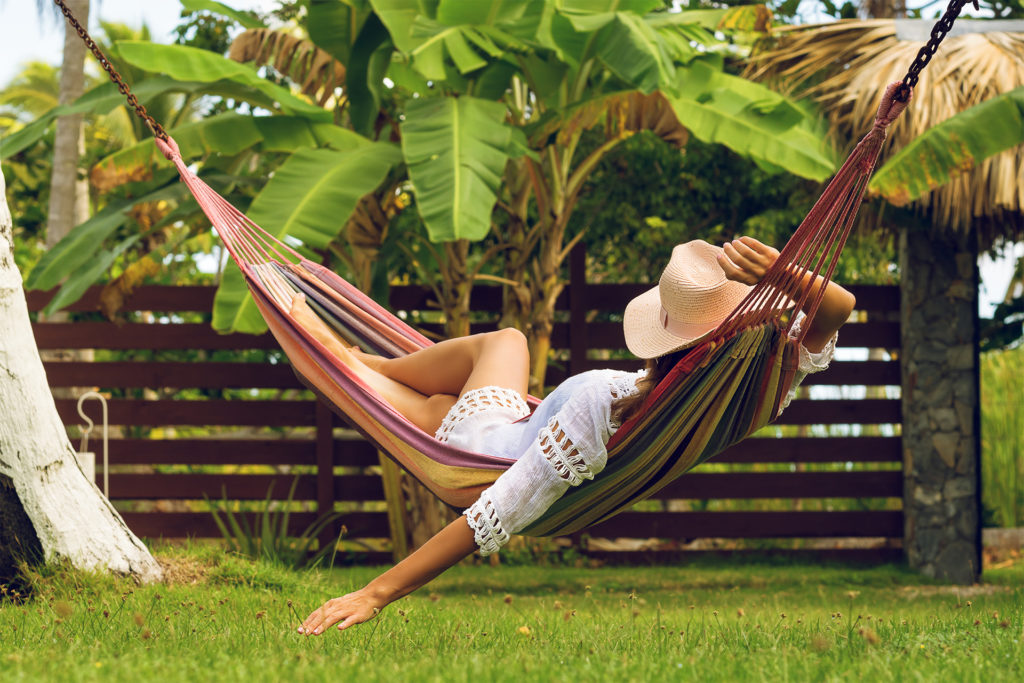 Woman in hammock in garden,, palm tree behind