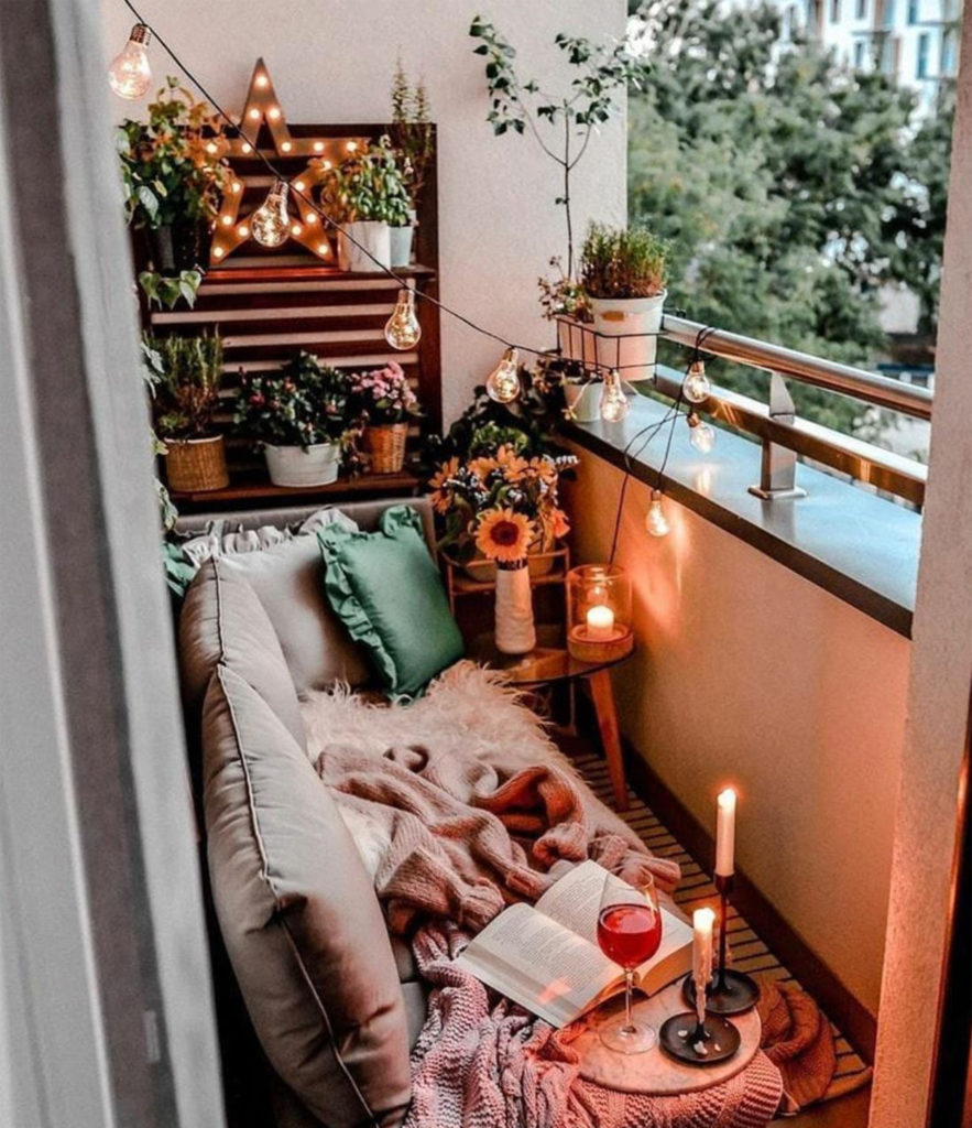 Cosy balcony with plants, bench with throw and candles