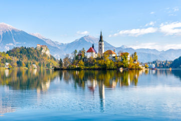 Lake Bled, fairytale towers and steep roofs on wooded island reflected in clear lake