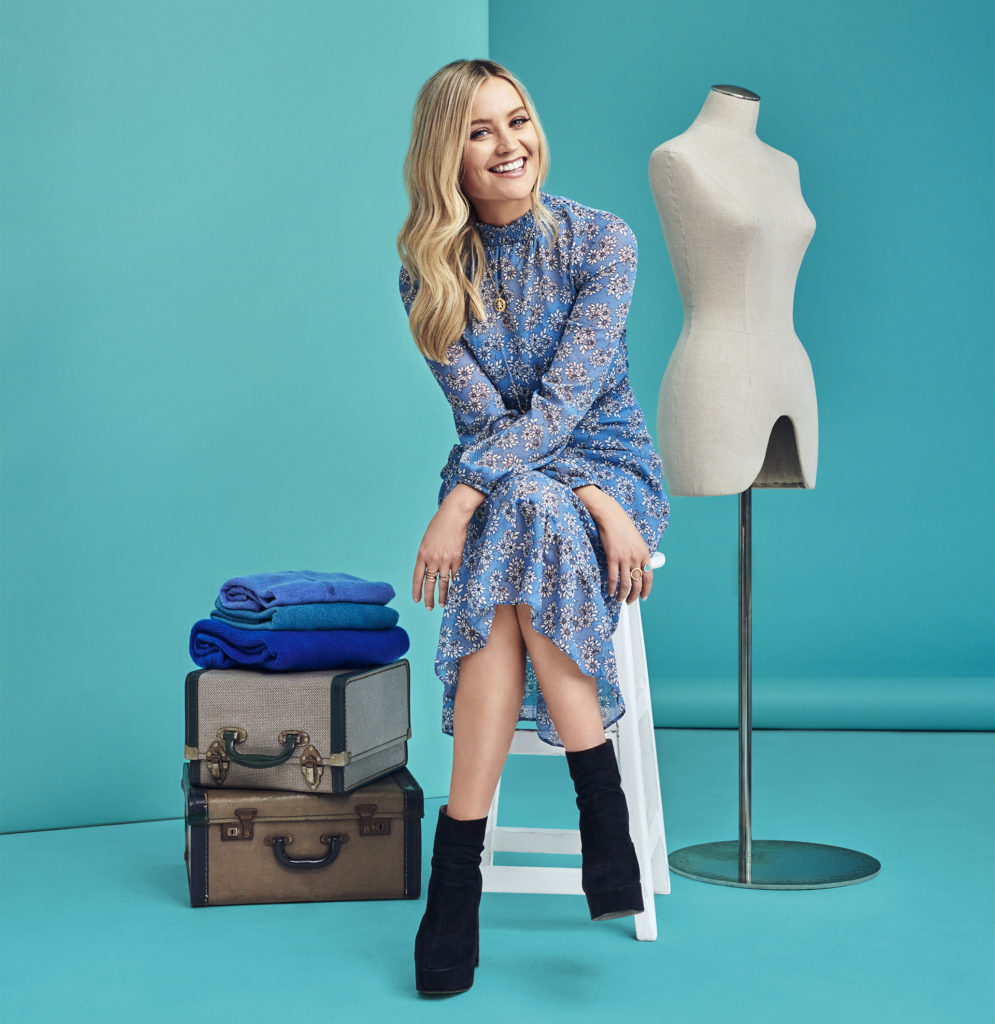 Young blonde woman in black ankle boots and high necked, long sleeved blue floral dress, sitting on stool, turquoise background