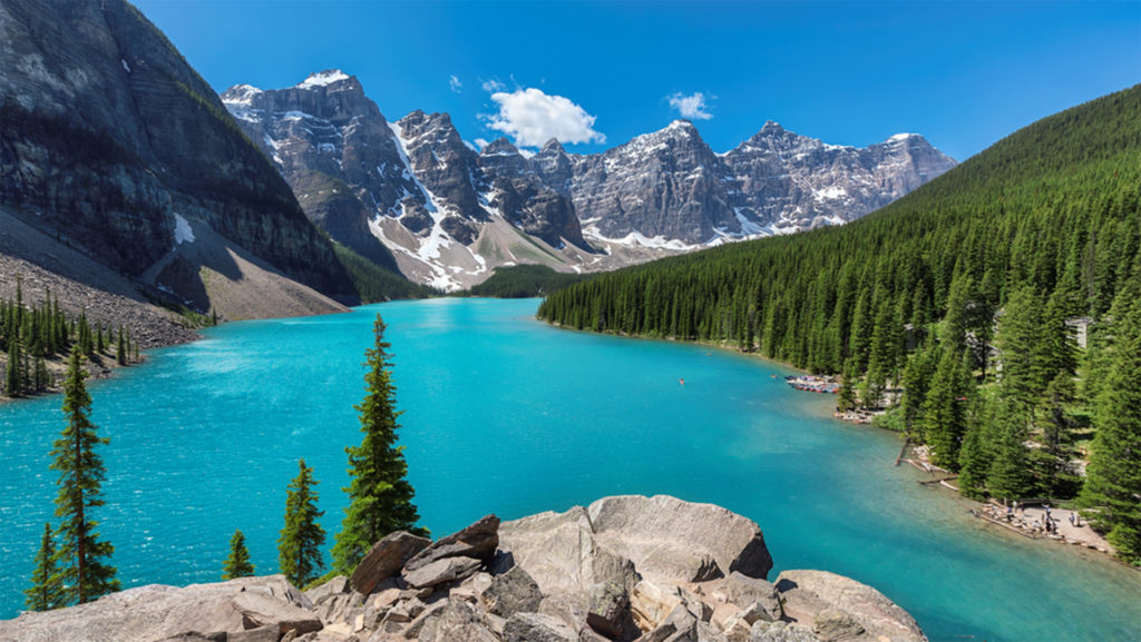 Bright turquoise lake, snow-dusted mountains beyond, forest and rocky shore