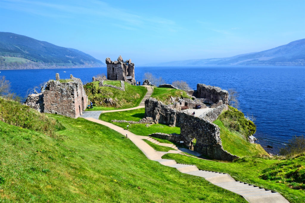 Castle ruins, green grass, blue loch and distant hills