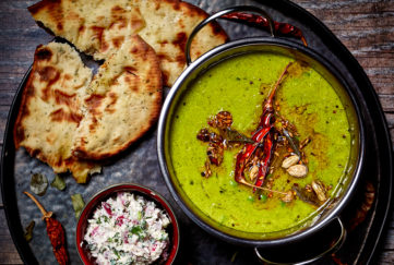 Bowl of beauriful pea green dip garnished with dried chilli and other spices, pot of white coconut chutney and golden toasted naan bread