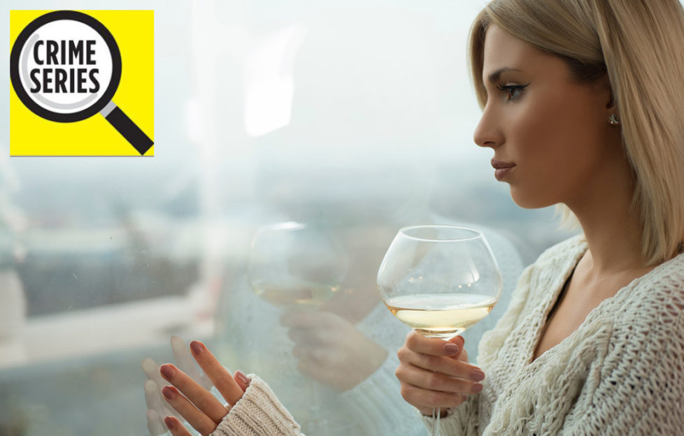 Elegant woman with glass of wine looks out of window