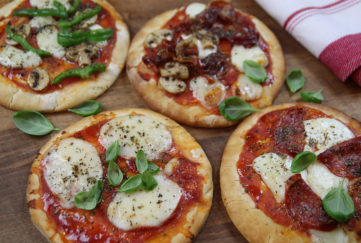 4 mini pizzas topped with tomato sauce, mozzarella slices, fresh basil and parma ham