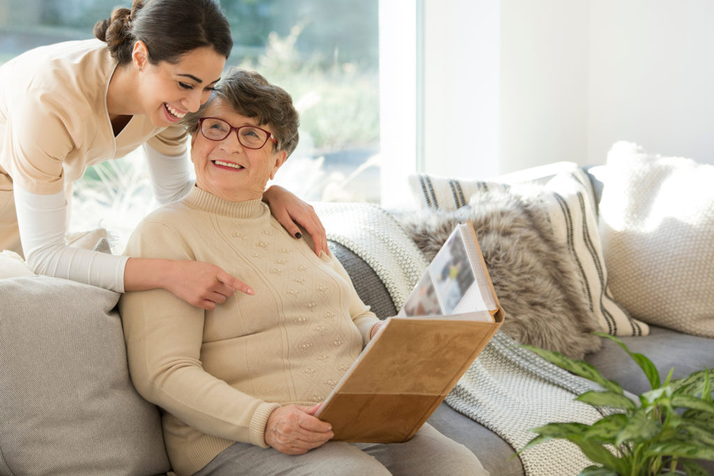 Grandmother sitting on a couch in a sunny room, looking at a photo album and sharing fond memories with a tender caregiver;