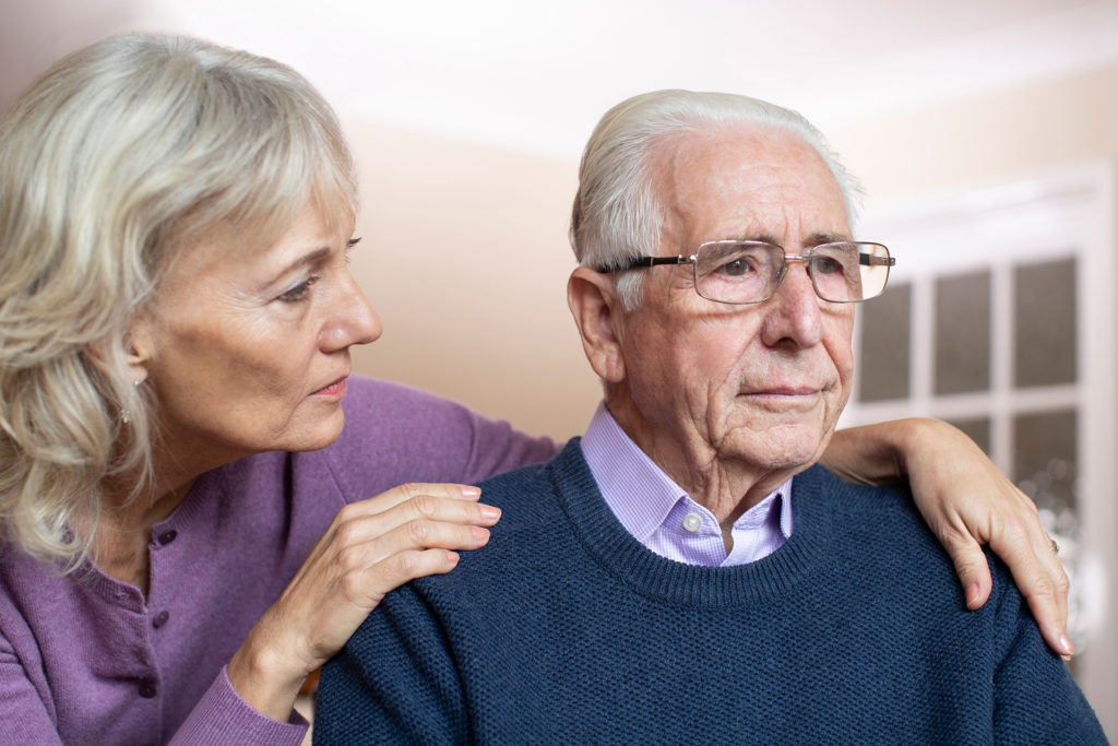 Confused Senior Man Suffering With Depression And Dementia Being Comforted By Wife;