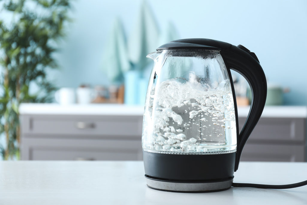 Transparent electric kettle with boiling water on table in kitchen;
