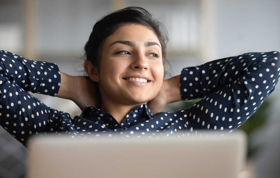 Happy satisfied indian woman rest at home office sit with laptop hold hands behind head, dreamy young lady relax finished work feel peace of mind look away dream think of future success concept;