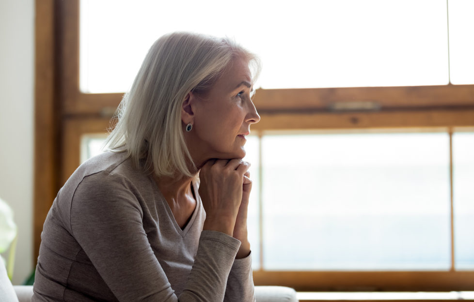 Side view of sad thoughtful middle-aged mature woman sit on couch at home look in window distance mourning, upset pensive senior female lost in thoughts thinking or pondering over past;