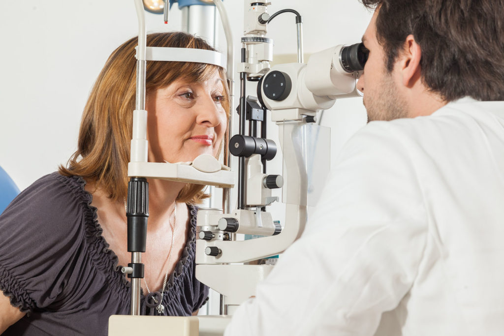Ophthalmologist In Exam Room With Mature Woman Sitting In Chair Looking Into Eye Test Machine;