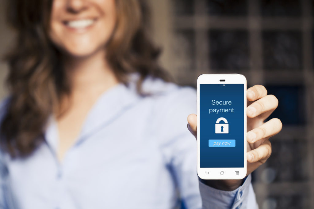 Secure payment message on a mobile. Smiling woman holding mobile phone screen