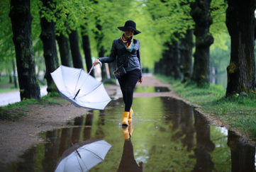 Woman in yellow wellies walking through puddles in park