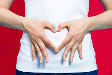 young woman who makes a heart shape by hands on her stomach.;