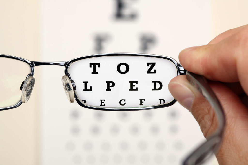 Looking through glasses at an eye exam chart;