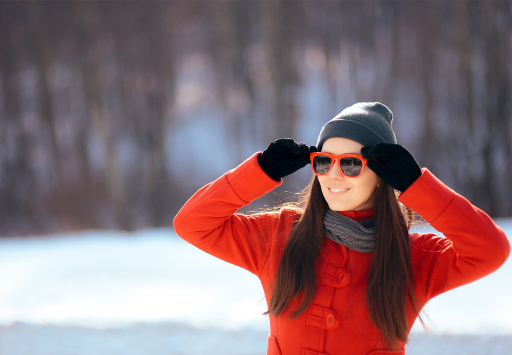 Woman in hat, scarf, red jacket and red framed sunglasses in snow