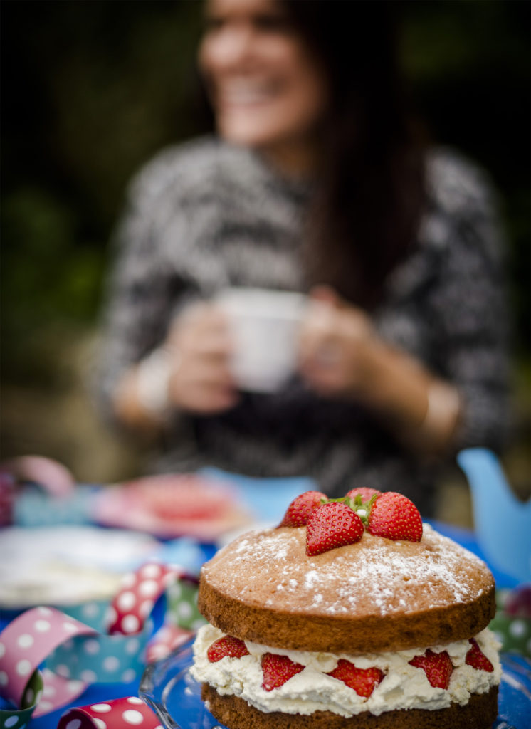 Strawberry and cream sponge with smiling woman in background