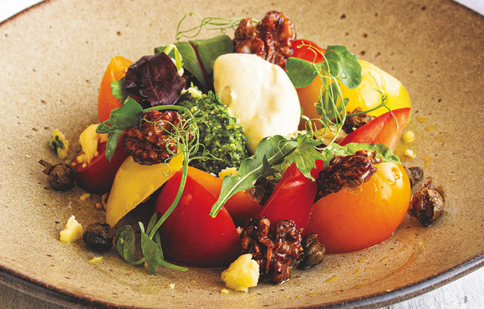 Colourful plate of salad with red and yellow tomatoes, green leaves and creamy white mousse