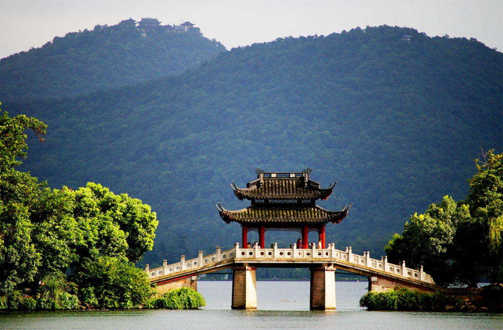 Chinese bridge and pagoda across lake, misty blue mountain beyond