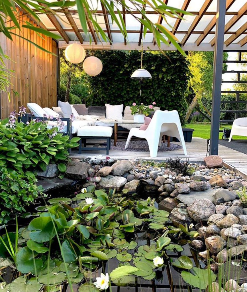 Seating area with roof and one wall, lawn and shrubs beyond, pond with lilies in foreground