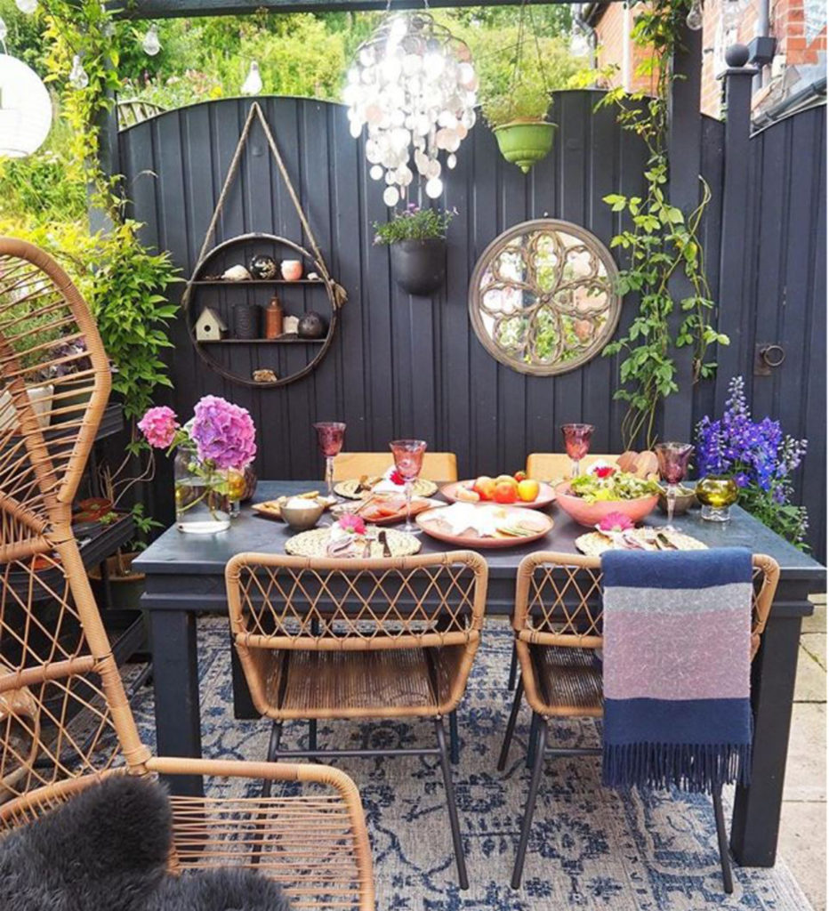 Table and chairs on patio, high grey fence with mirror, climbing plants and decorative shelves