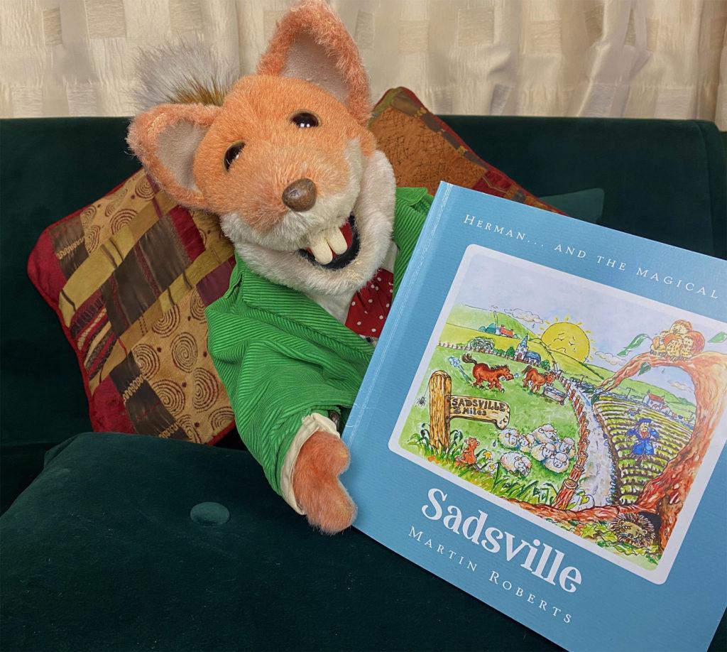 Puppet character Basil Brush holding children's book Sadsville