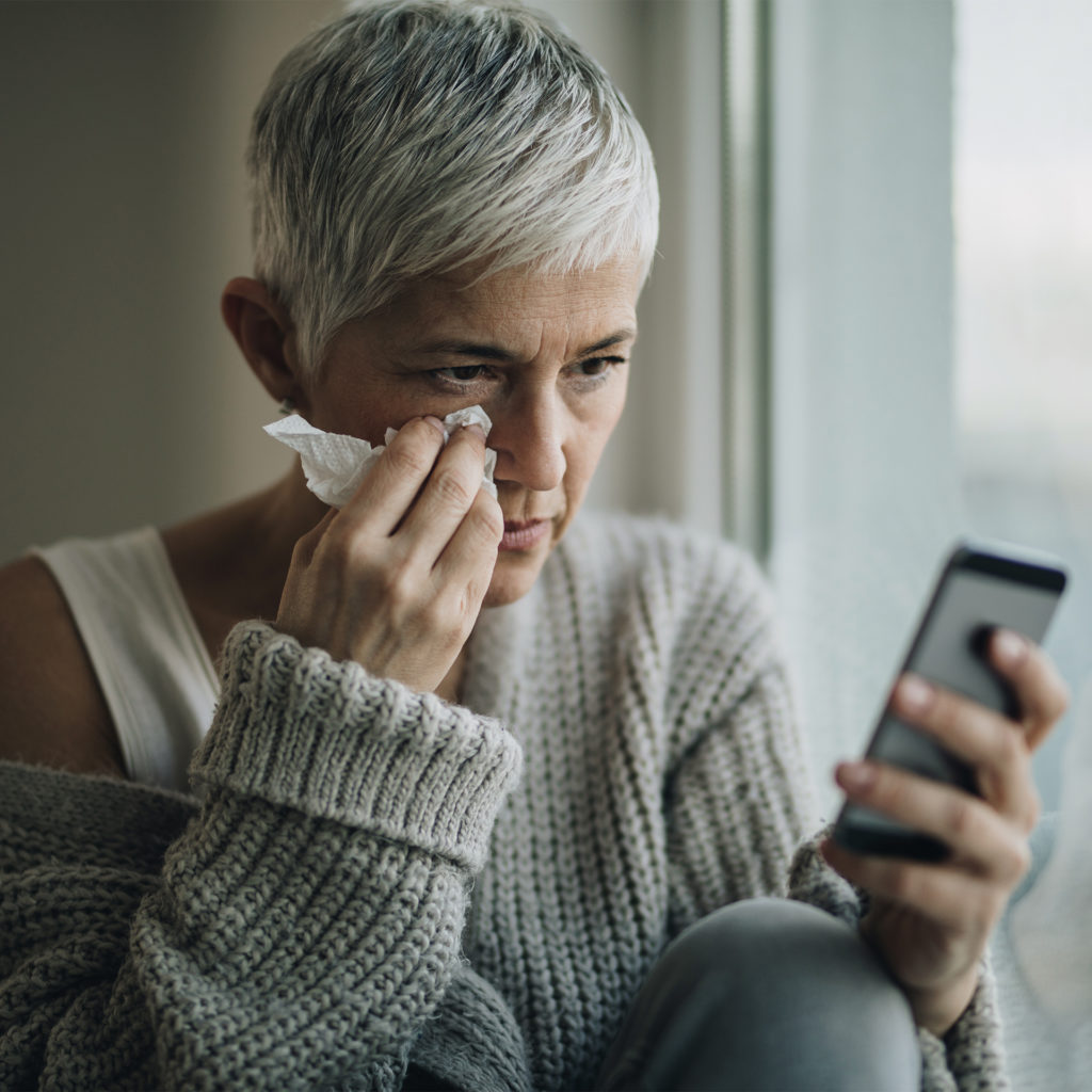 Depressed mature woman reading bad news on mobile phone while sitting by the window.