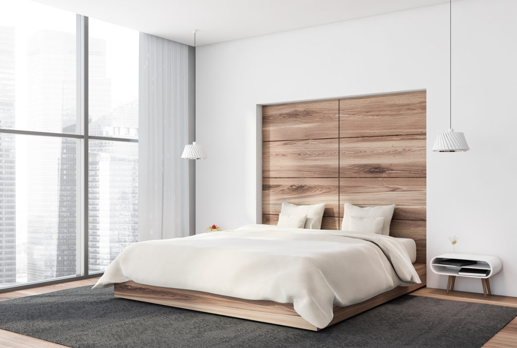 Corner of panoramic bedroom with white and wooden walls, wooden floor, king size bed with white blanket standing on carpet and window with blurry cityscape.