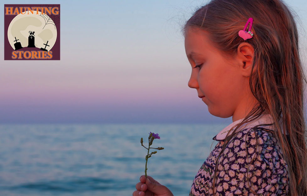 Girl aged around 8 stands by sea at dusk, looking at wild flower, she has long hair and a traditional summer dress with floral print and white collar