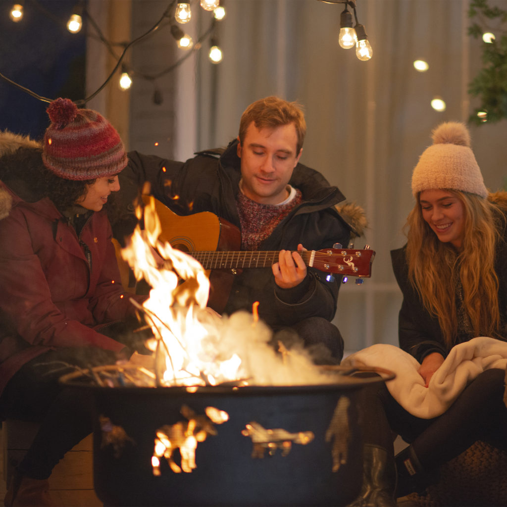 Multi-ethnic group of young adults enjoy an outdoor fire together.
