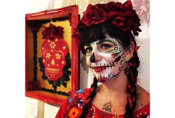 Dia de los muertos. Woman with crown of roses and skull facepaint with colourful artwork of a skull