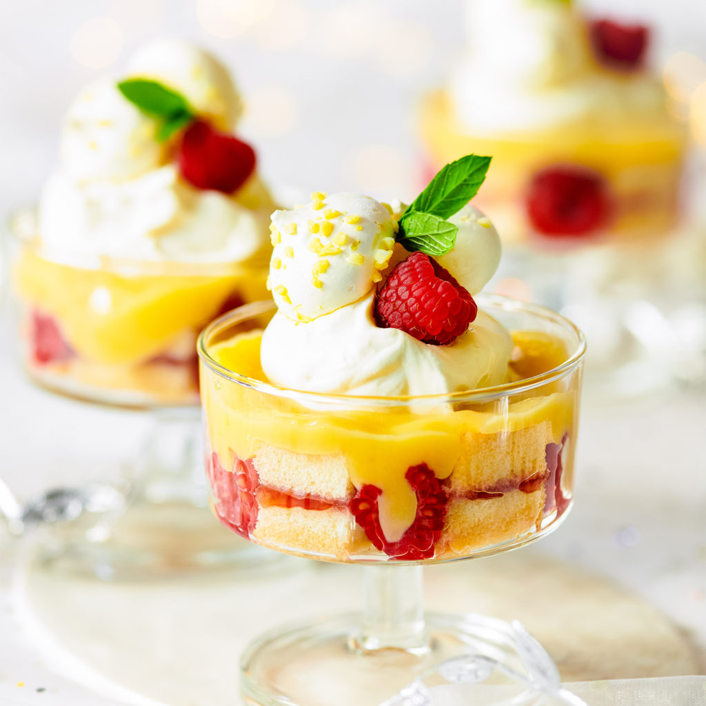 Glass dishes with individual trifles, raspberry halves against dish sides, golden custard, piped cream and raspberries on top