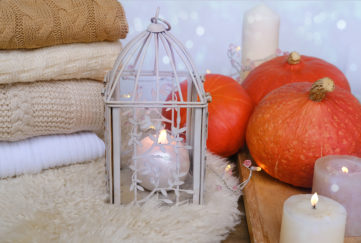 Folded blankets, sheepskin rug, candles and pumpkins, white decor