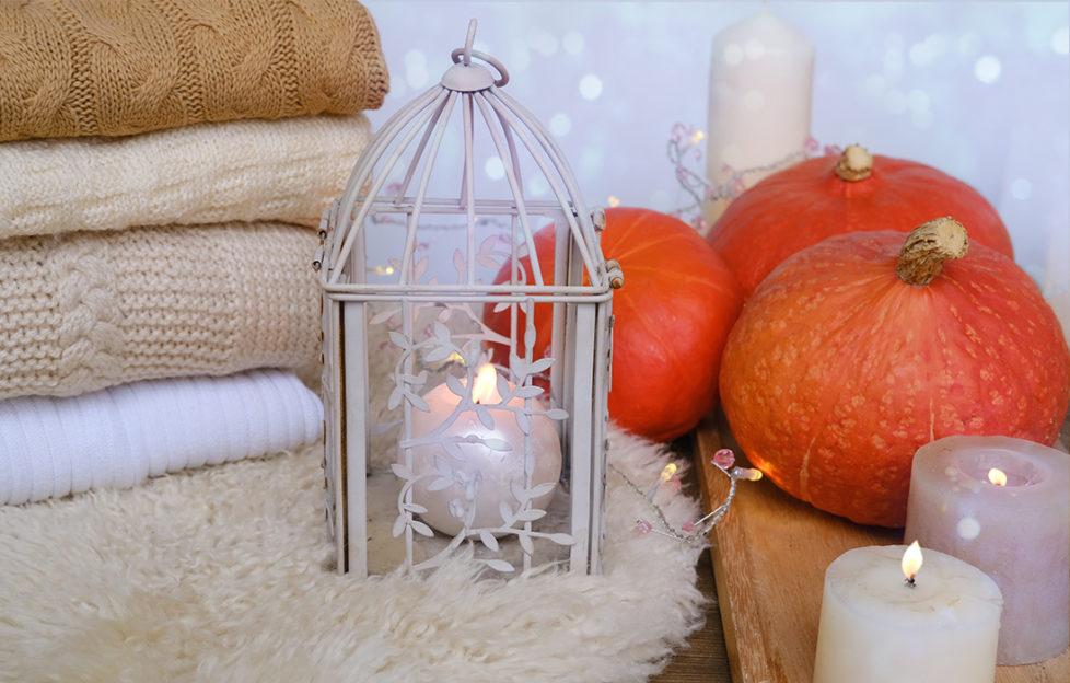 Folded blankets, sheepskin rug, candles and pumpkins, white decor