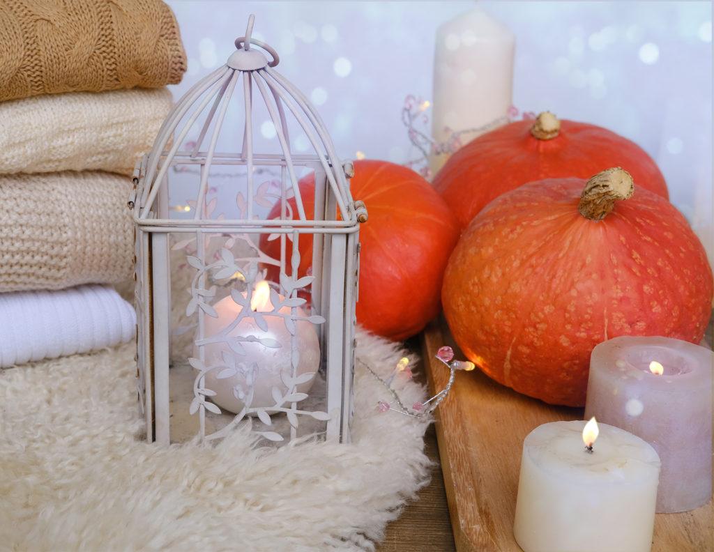 cozy Scandinavian hyugge, three orange pumpkins, white candles, woolen clothes, sheepskin, halloween concept, cozy home, aromatherapy